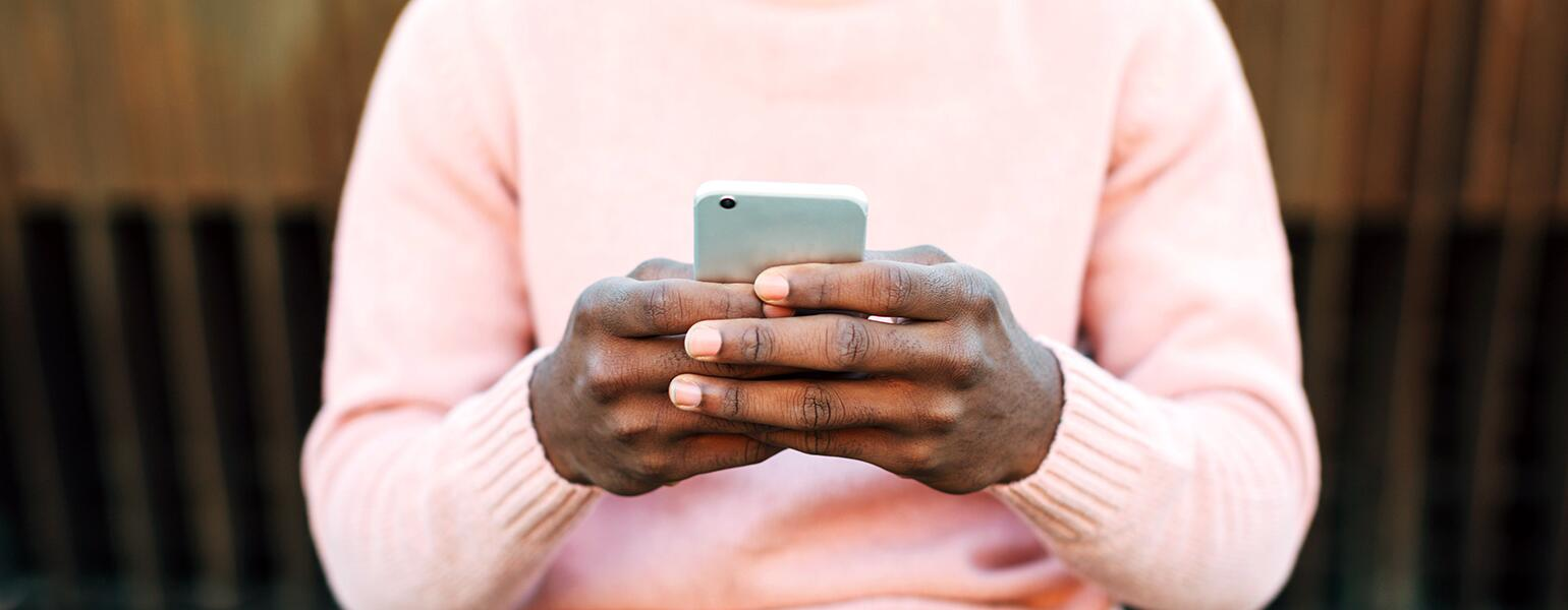 A man holds a cellphone, typing to an unknown person while sitting outside.