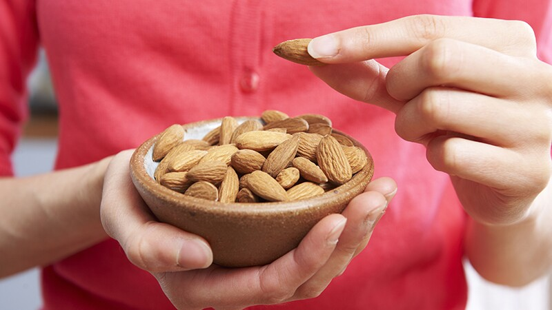 A woman holding a bowl of almonds in her hand