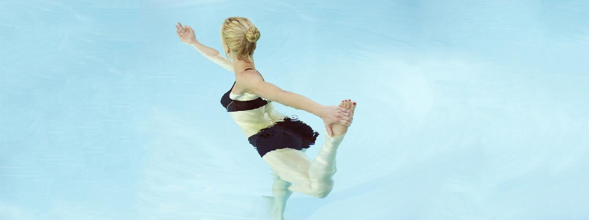 Mid adult woman holding her foot while practicing yoga in a swimming pool