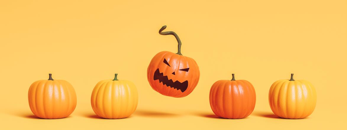 Row of pumpkins with one with angry face on orange background.