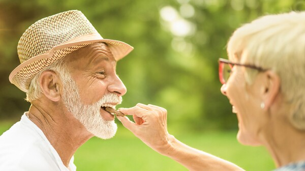 A happy woman putting a piece of chocolate in a man's mouth