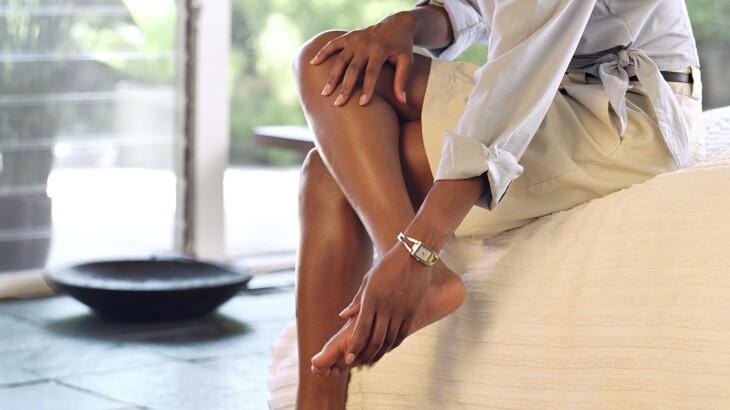 woman taking off high heels rubbing her feet