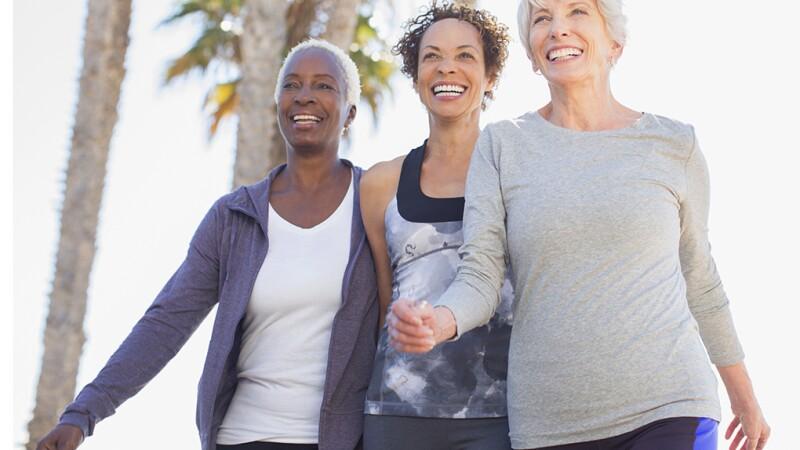 three women walking on sunny day