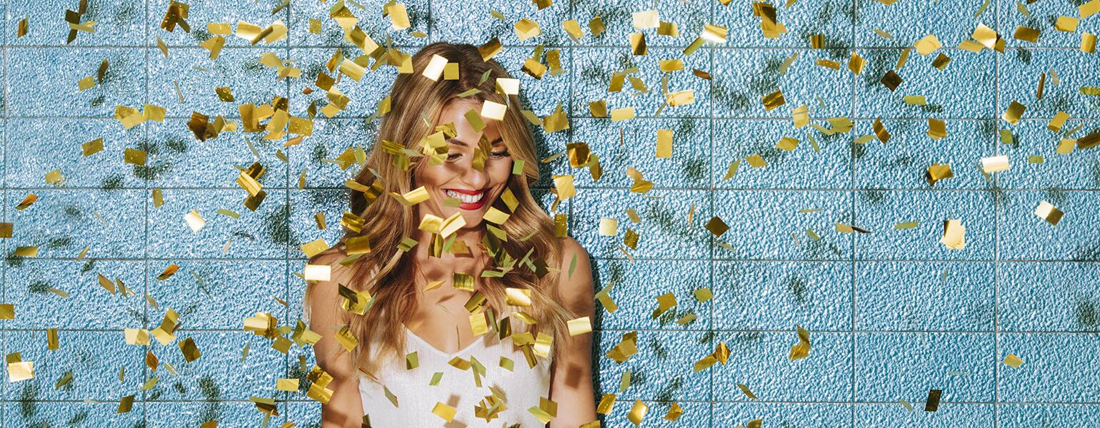 Single woman smiling with confetti falling down around her