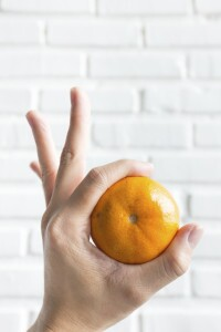 Holding orange on white brick background