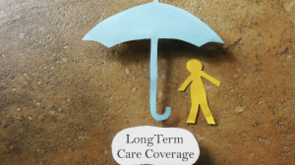 Paper person under an umbrella with Long Term Care Coverage text -- elder care insurance concept