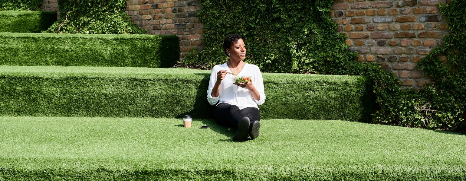 A woman practicing mindful eating sitting in the grass