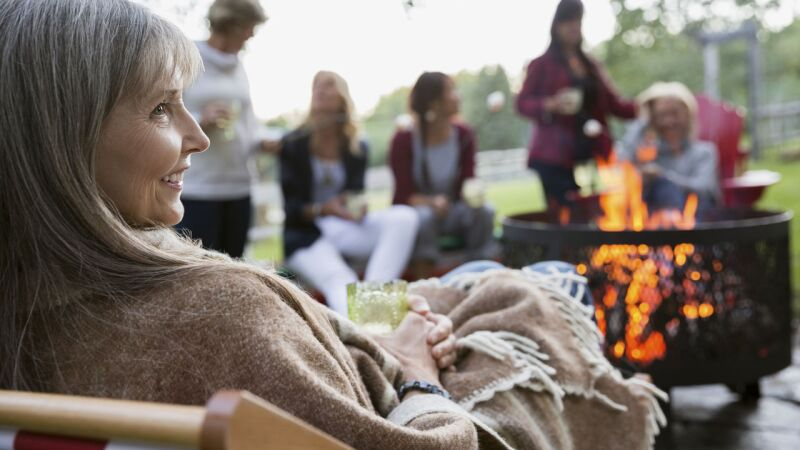 women relaxing around fire pit in backyard