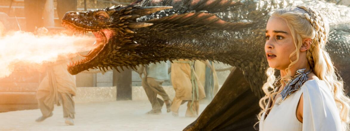 game of thrones character Daenerys Targaryen standing next to a fire breathing dragon