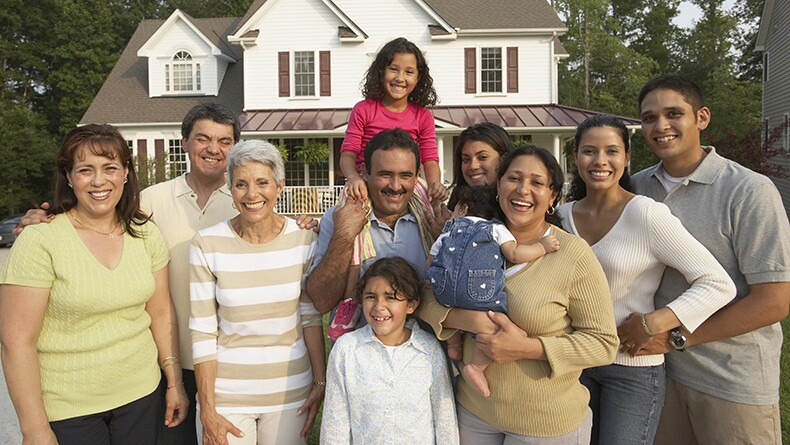 Multi-generational Hispanic family smiling in front of house