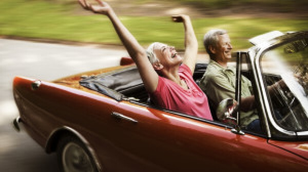 Couple driving in red convertible