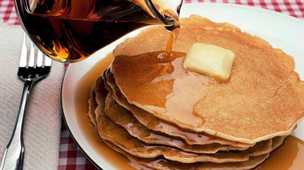 maple syrup being poured over pancakes