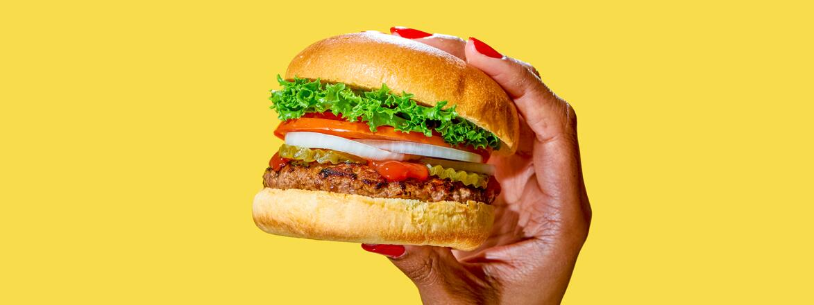 African American woman's hand holding a delicious looking burger