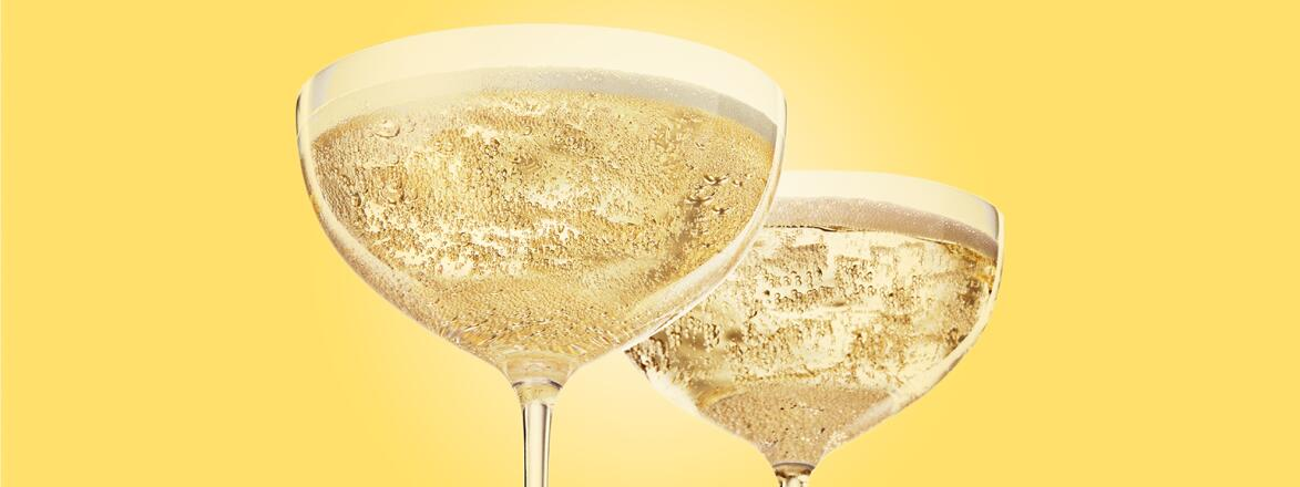 two glasses of champagne with a yellow background
