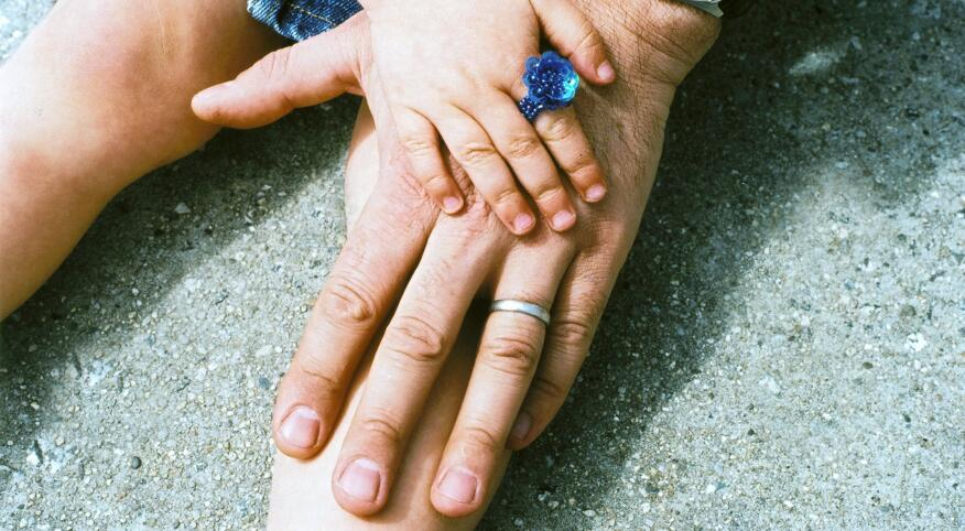 small toddler hand on top of her fathers hand