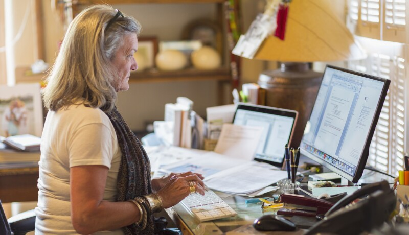 older Caucasian woman sits at a computer with paperwork around her