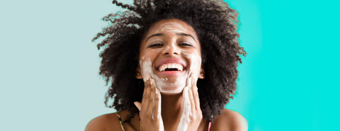 A woman washing her face to combat signs of aging.