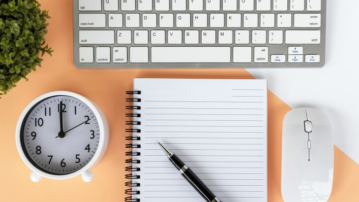 image_of_flat_lay_of_notebook_clock_keyboard_GettyImages-1152254894_1800