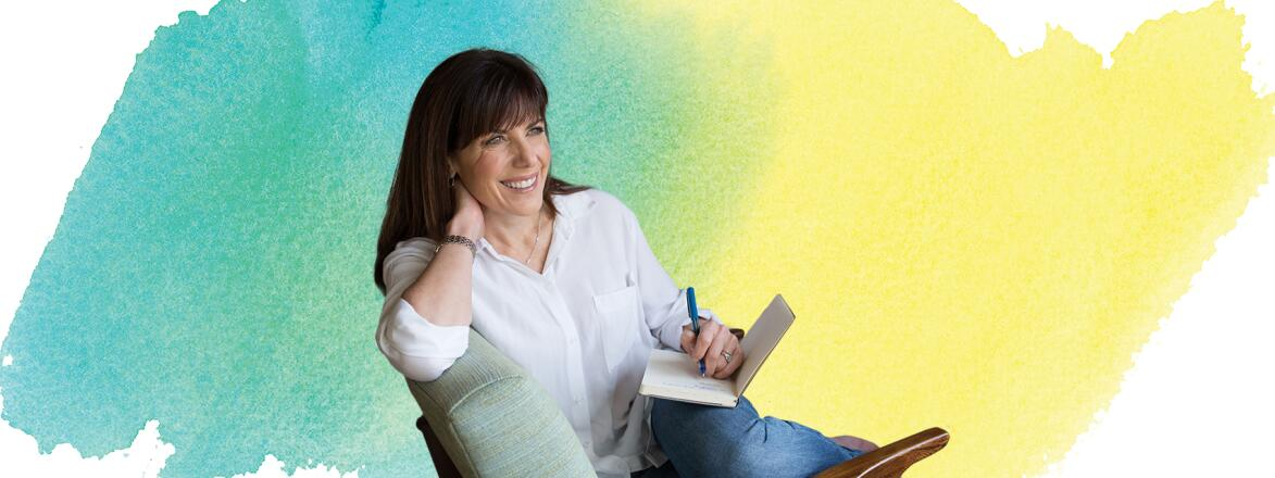 Jean Chatzky sitting in a chair writing in a notebook with water color background