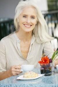 Senior Woman Enjoying Snack At Outdoor Café