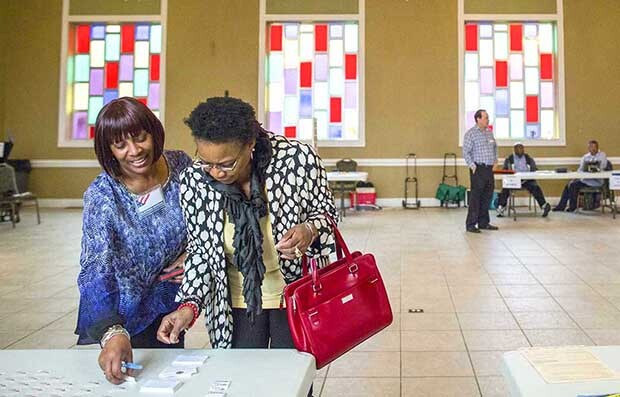 Sandy Haddock and Shirlee McCleskey talk at the Cathedral of Praise church, a polling station in Nashville, Tenn.