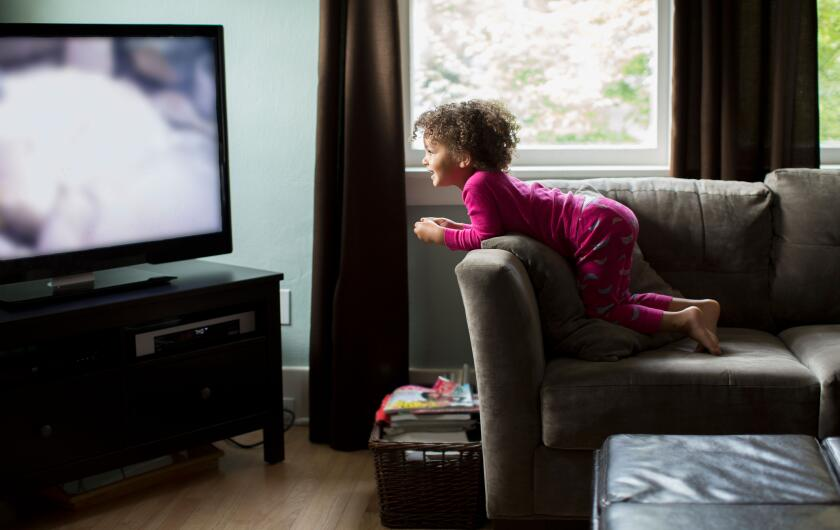 Let-go-of-perfection-little-girl-watching-tv-from-sofa-smiling-GettyImages-155770683.jpg