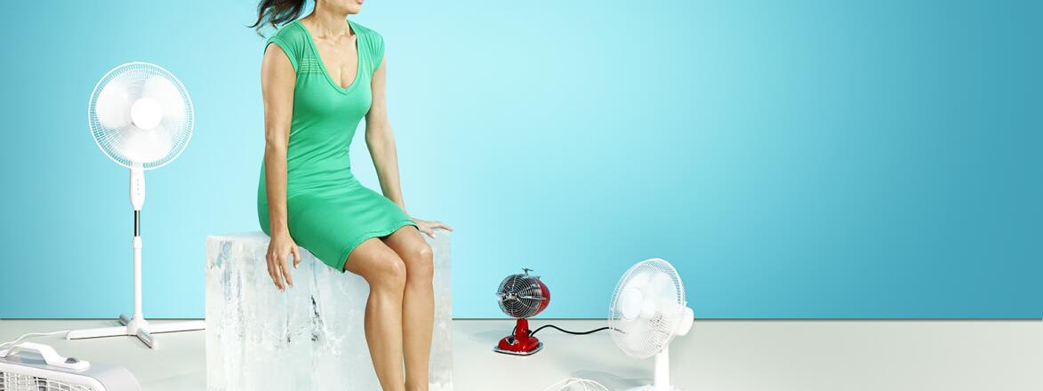 A woman in perimenopause sits surrounded by fans to combat her hot flashes.