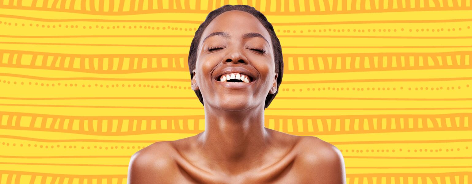 woman smiling with clear skin on yellow background