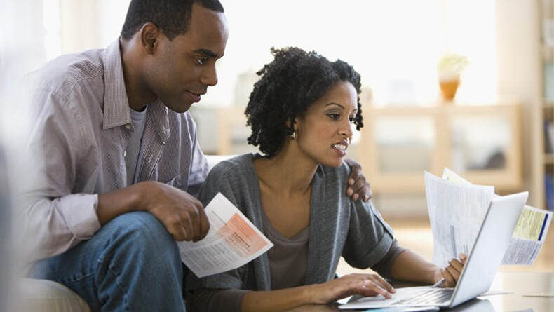 A Black couple sits together and looks at a computer screen while holding bills