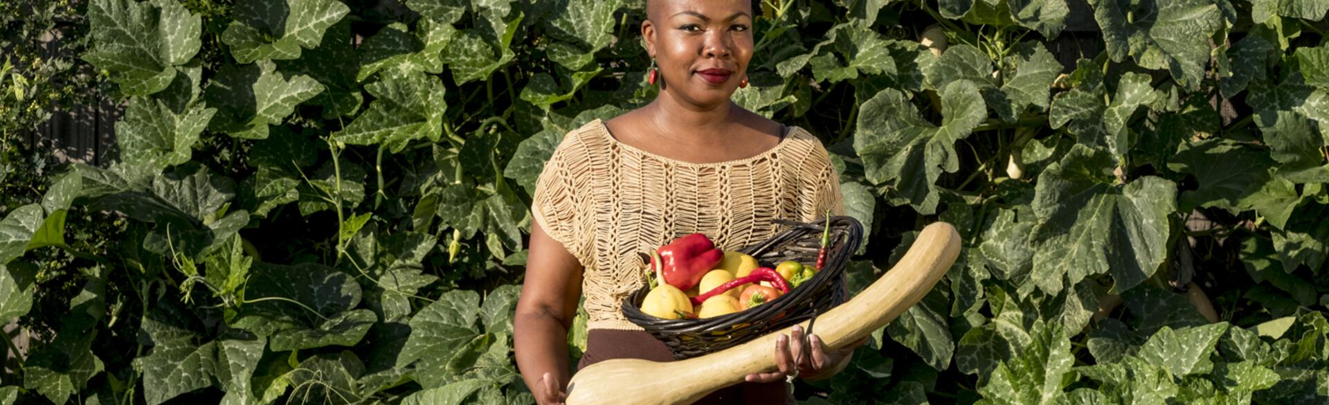 author towanna standing outside holding vegetables she grew in her garden
