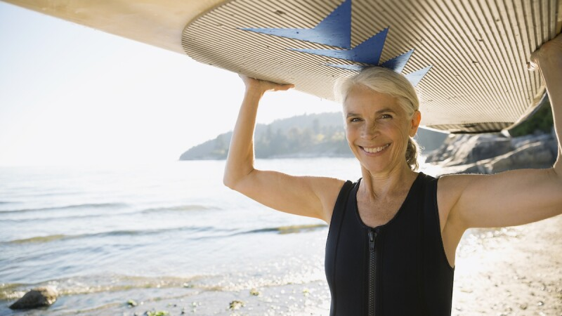 A woman carrying a surfboard above her head on the beach