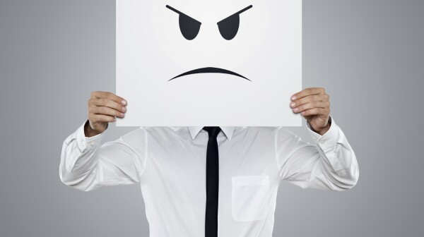 Young businessman holding card with a angry face on it isolated