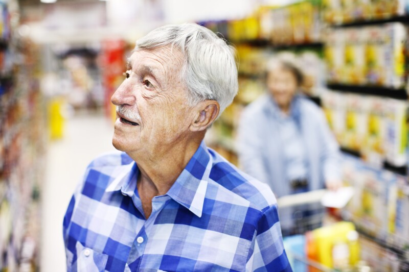 Serious senior man checks supermarket shelves seeking something