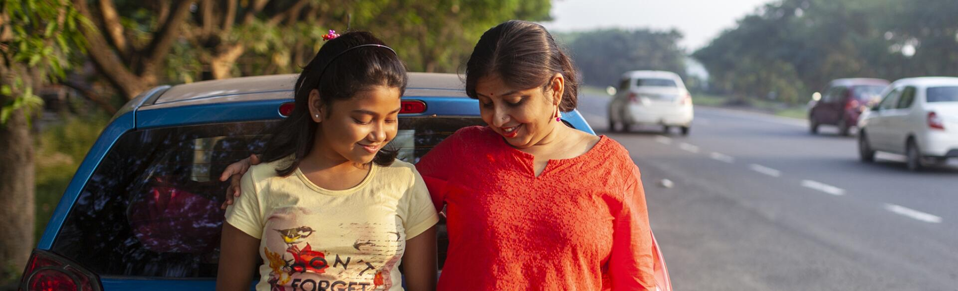 Mother And Daughter Standing Beside A Highway And Interacting