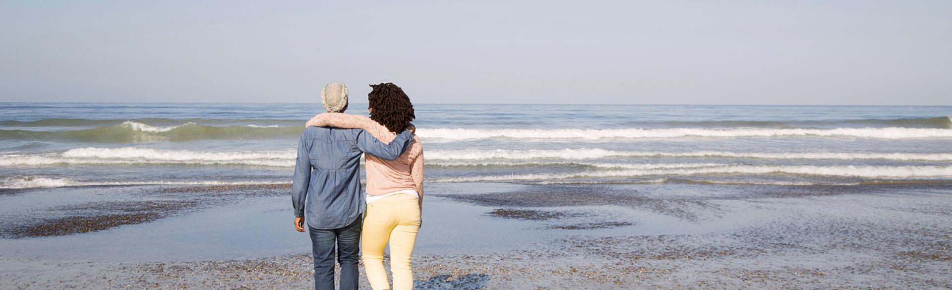 Black women hugging and walking on beach