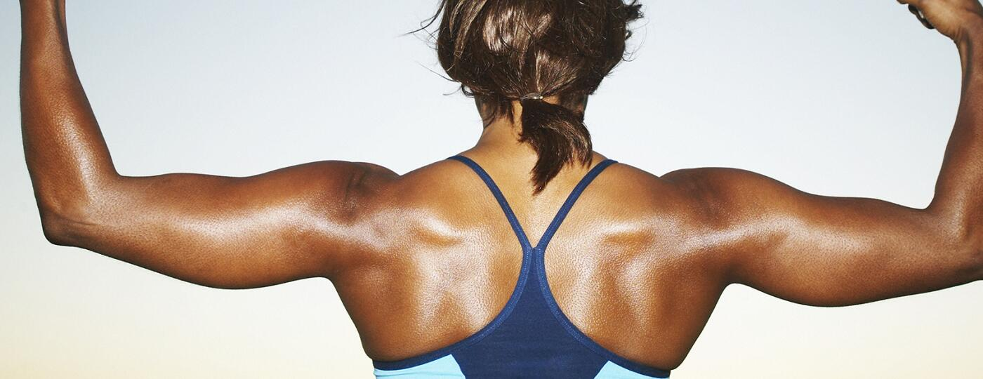 Woman bodybuilder flexing arms, top section, rear view