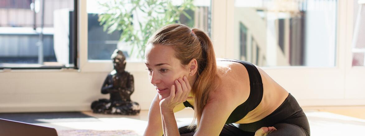 Woman exercising at home in front of her laptop, choosing online yoga class