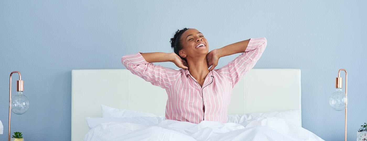 image_of_woman_smiling_stretching_in_bed_GettyImages-1133811946_1800