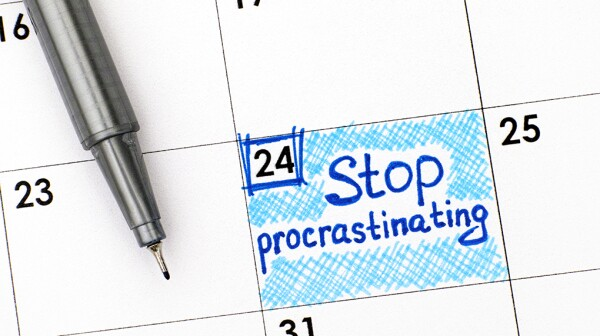 "A close-up view of a calendar with ""Stop procrastinating"" written on it"
