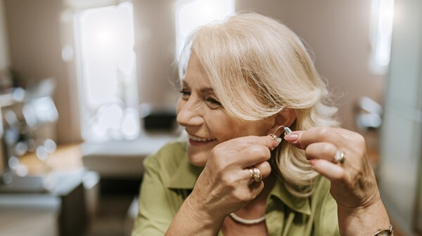 A smiling woman putting a hearing aid in her ear