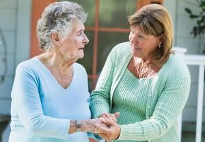 Caregiver helping senior woman on a walk