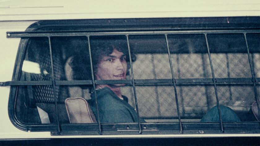 Richard Ramirez, a nocturnal serial killer, sits behind bars inside a police vehicle.
