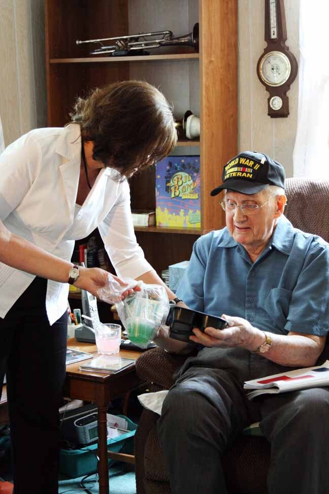 A Meals On Wheels volunteer serves a member of the greatest generation