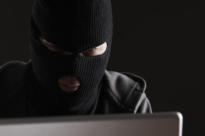Masked Man Accessing Computer Data