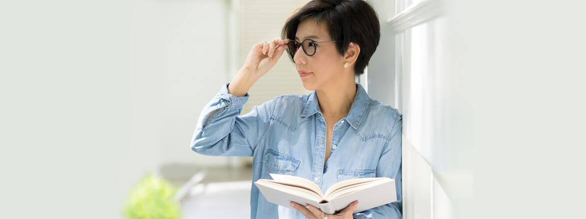 woman standing reading a book with her glasses