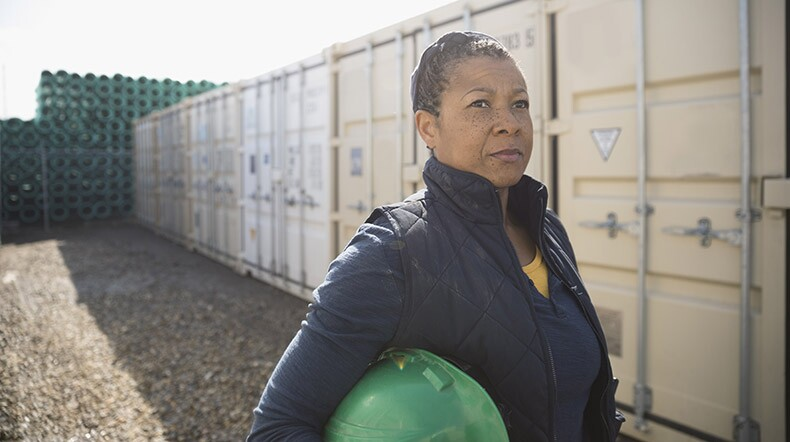Serious female African American worker in industrial container yard