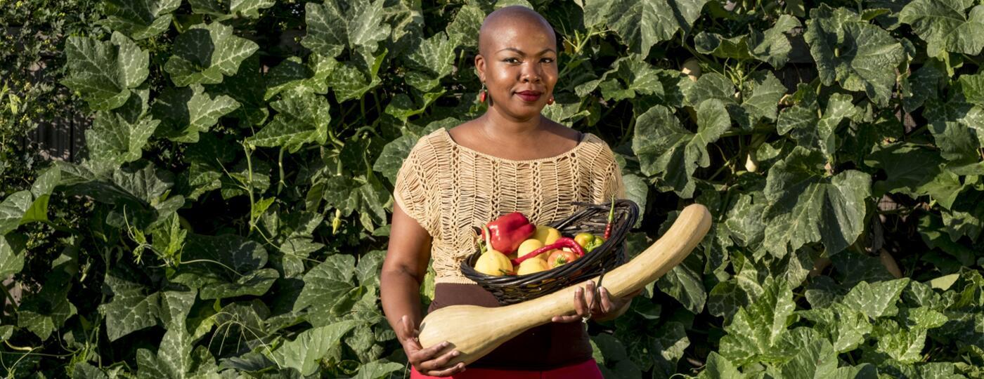 author towanna standing outside holding vegetables she grew in her garden