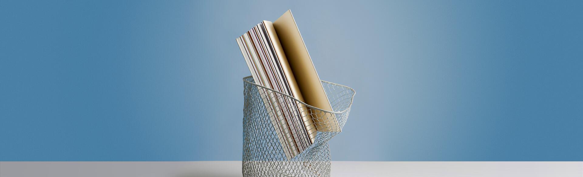 Large book in wastepaper basket