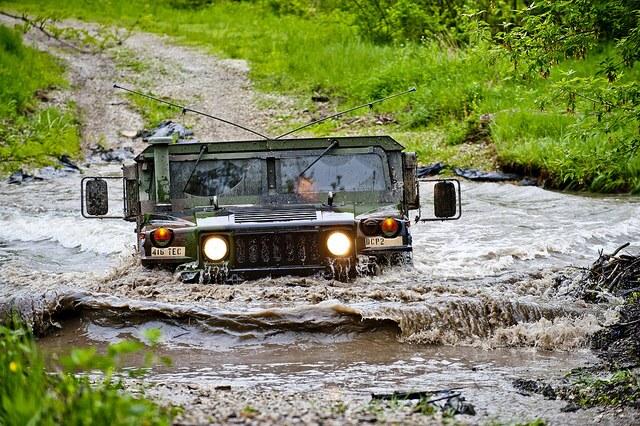 Humvee driving through creek
