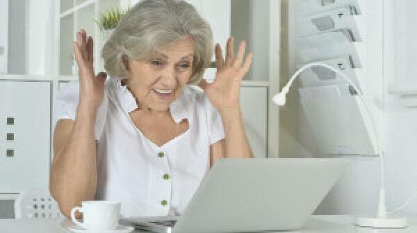 Happy surprised Elderly woman working on laptop
